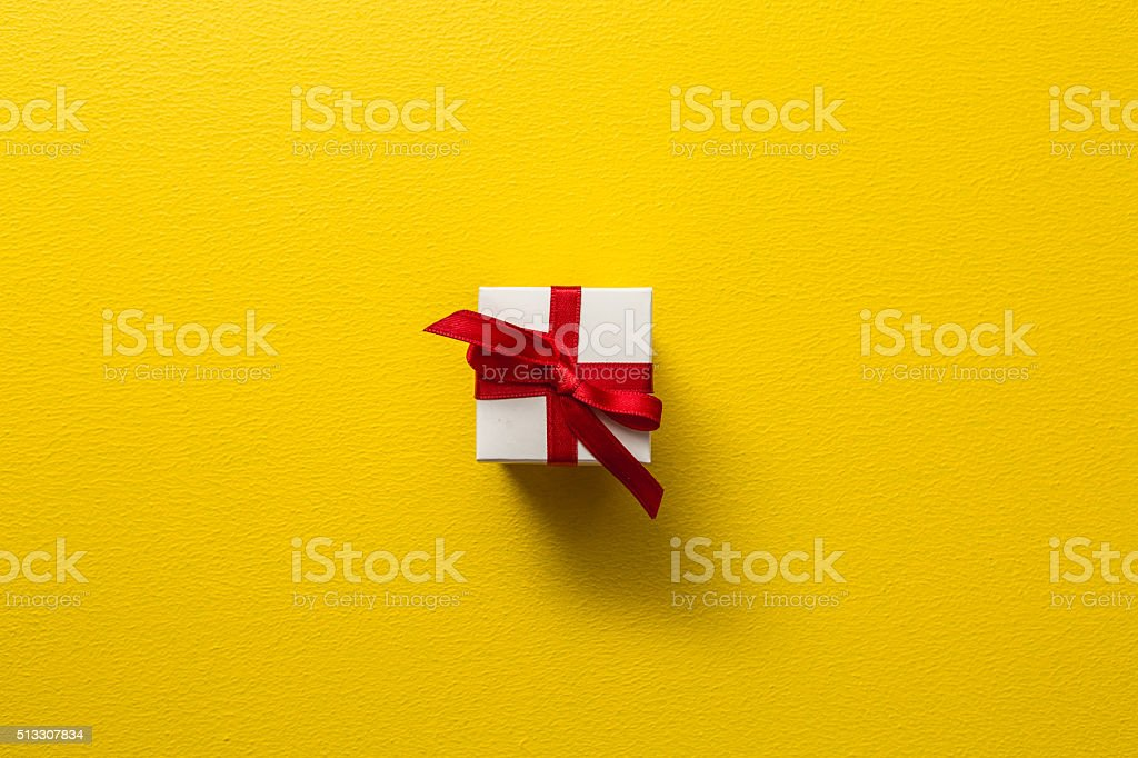 Christmas gift box on yellow background stock photo