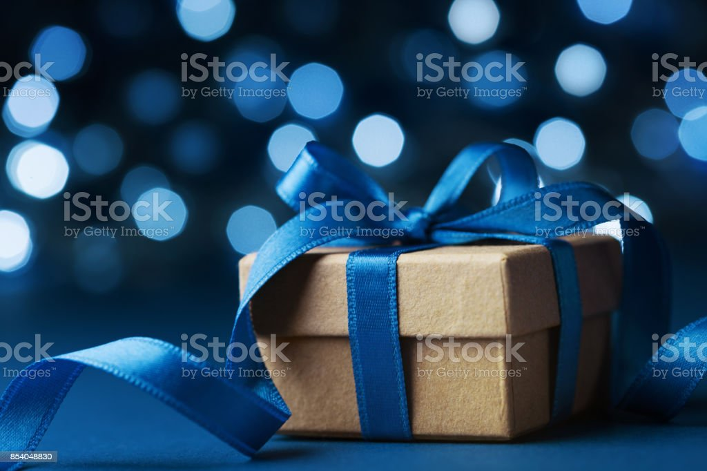 Christmas gift box or present against blue bokeh background. Holiday greeting card. stock photo