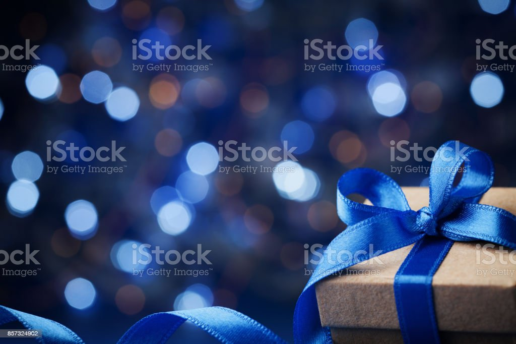 Christmas gift box or present with bow ribbon on magic blue bokeh background. stock photo