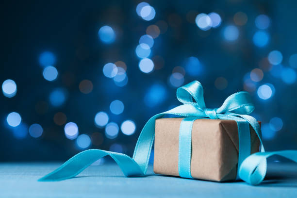 Christmas gift box or present with bow ribbon on magic blue bokeh background. Christmas gift box or present with bow ribbon on magic blue bokeh background. Copy space for greeting card. birthday present stock pictures, royalty-free photos & images