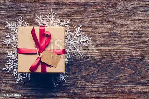Christmas gift box placed and white snowflakes on wooden planks with space.