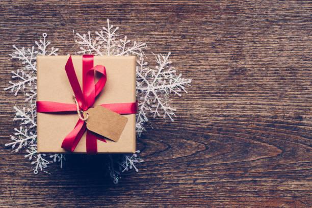 weihnachts-geschenk box platzierte und weiße schneeflocken auf holzbohlen mit platz. - sprüche über reisen stock-fotos und bilder