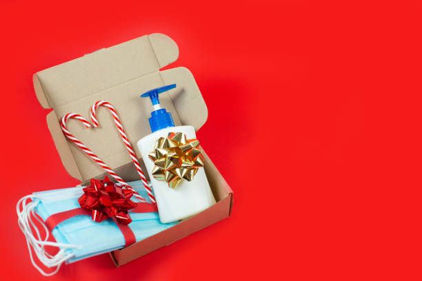 Christmas gift box with Disposable face masks, Hand sanitizer and candy cane stock photo