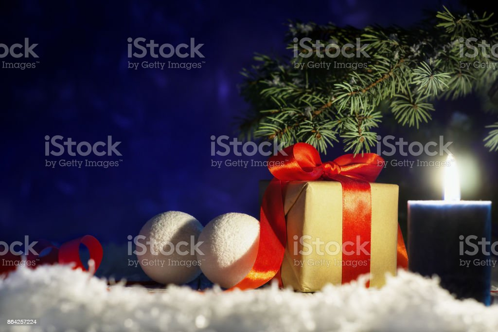 Christmas gift box with red ribbon and balls on snow on night background. royalty-free stock photo