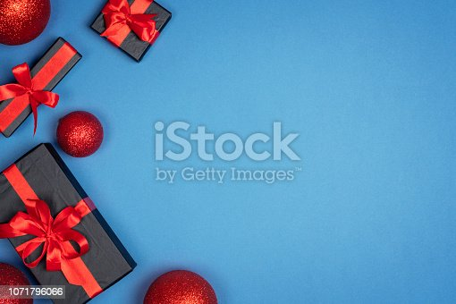 1076063742 istock photo Christmas gift box with red ribbon on blue background. Holiday new year Top view with copy space for your design 1071796066