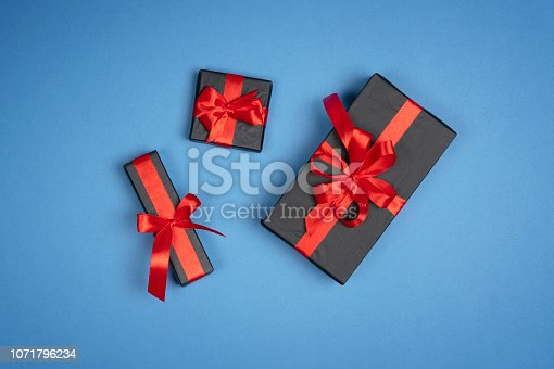 1076063742 istock photo Christmas gift box with red ribbon on blue background. Holiday new year Top view with copy space for your design 1071796234