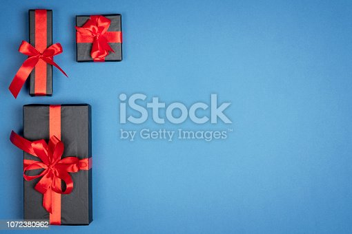 1076063742 istock photo Christmas gift box with red ribbon on blue background. Holiday new year Top view with copy space for your design 1072380962