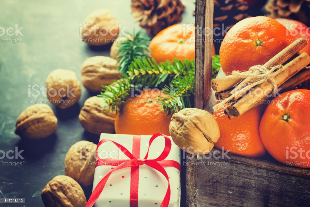 Christmas Gift Box with Red Silk Ribbon Tangerines Cinnamon Sticks Fir Tree Branches Pine Cones Walnuts in Wood Box Black Background Greeting Card Poster Copy Space stock photo