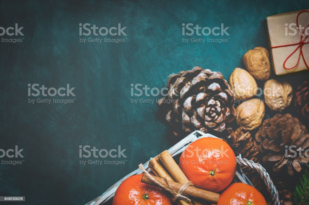 Christmas Gift Box with Red twine Tangerines Cinnamon Sticks Fir Tree Branches Pine Cones Walnuts Dark Blue Background Greeting Card Poster Copy Space stock photo