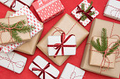 istock Christmas gift box wrapped in ornament paper and decorative red rope ribbon on red surface. Creative hobby, top view. Prepare to Xmas. 1044172350
