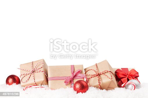 Christmas gift boxes and decor in snow. Isolated on white background
