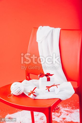 Christmas gift boxes and festive decorations on white scarf on the red chair.
