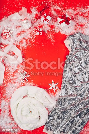 Festive Christmas attributes and decorations on a red background. Gift boxes and sequin dress on the snow.