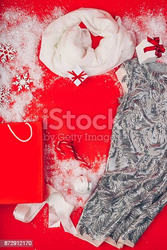 Festive Christmas attributes and decorations on a red background. Gift boxes and sequin dress on the snow. Red paper package.