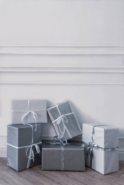 Christmas gift boxes in front of white wall stock photo