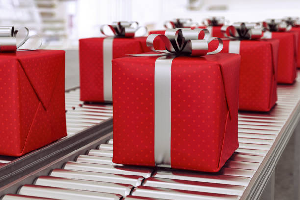 Christmas gift boxes on conveyor rollers ready to be shipped by courier for distribution stock photo