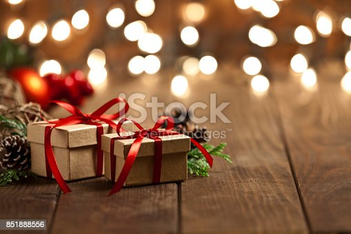 Horizontal view of two brown Christmas gift boxes shot on rustic wood table. The boxes are tied up with a red ribbon and Christmas lights are out of focus behind the group of boxes. The two boxes are grouped at the left side of the frame leaving a useful copy space ready for text and/or logo at the right. Predominant colors are brown and red. DSRL studio photo taken with Canon EOS 5D Mk II and Canon EF 70-200mm f/2.8L IS II USM Telephoto Zoom Lens