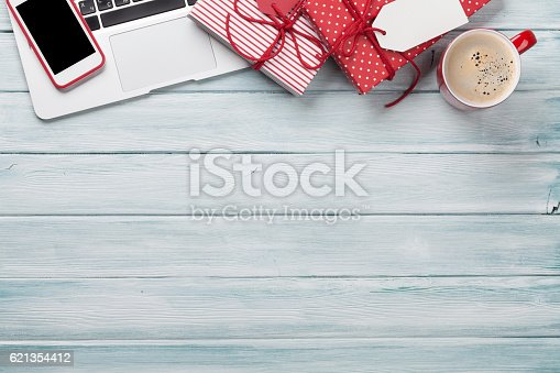 istock Christmas gift boxes, pc and coffee cup on wood 621354412