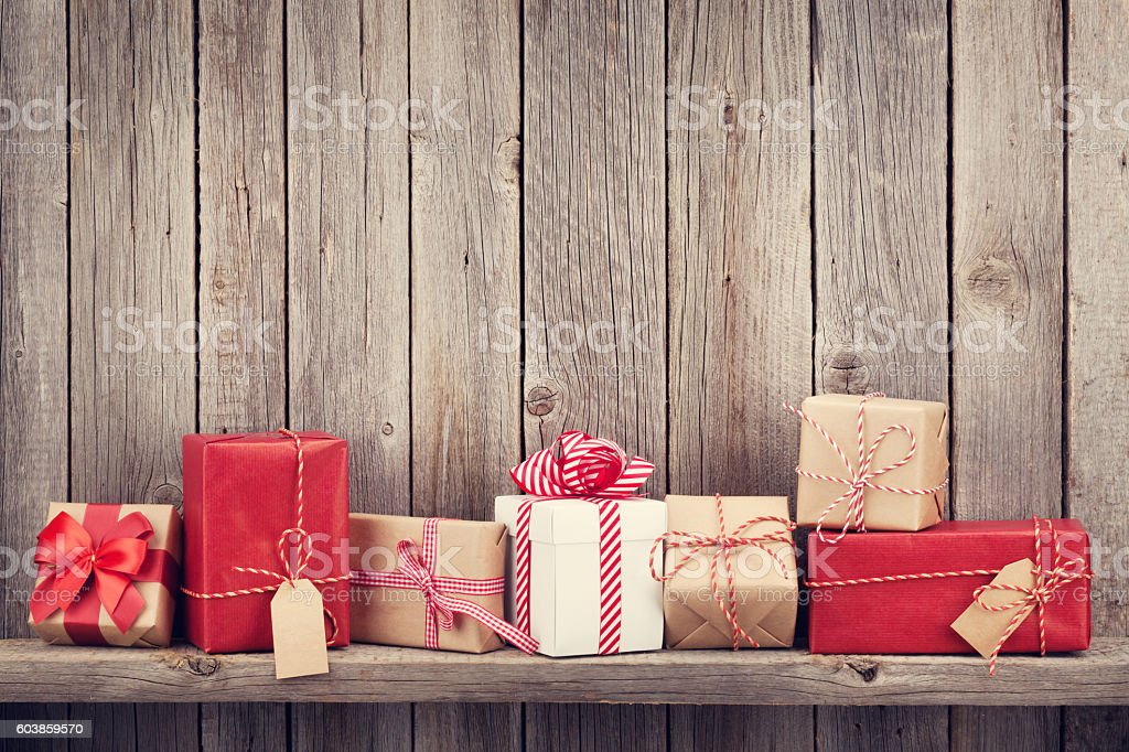 Christmas gift boxes Christmas gift boxes in front of wooden wall with copy space. Retro toned Advent Stock Photo