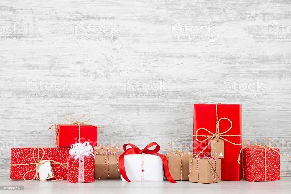 Christmas Gift Boxes Lots of Christmas gift boxes in front of a white rustic wooden background. 2017 Stock Photo
