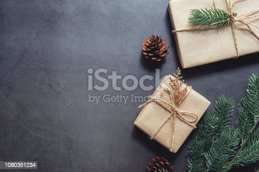 Christmas gift boxes pine branches on black background. Flat lay, top view