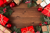 Christmas concept with Christmas Present, ornaments, and Christmas tree branches on wooden background.