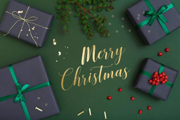 weihnachtsgeschenk flach zu legen, auf grünem hintergrund mit gruß weihnachtsbotschaft in der mitte - texte zu weihnachten stock-fotos und bilder