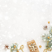 istock Christmas gift, green twigs and gold decorations on snowy white background. 1284596867