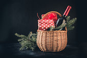 Christmas gift hamper with red wine and gift on black. Space for your greetings. Xmas.