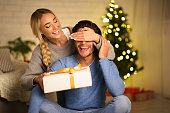 istock Christmas gift. Happy woman making surprise to husband 1178964685