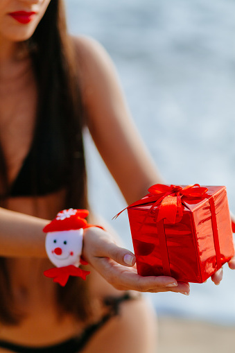 1155046257 istock photo Christmas gift in hands on the beach 527722579