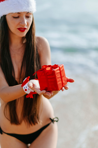 1155046257 istock photo Christmas gift in hands on the beach 528137083