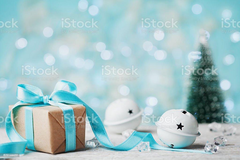 Christmas gift, jingle bells and blurred fir tree with bokeh. stock photo