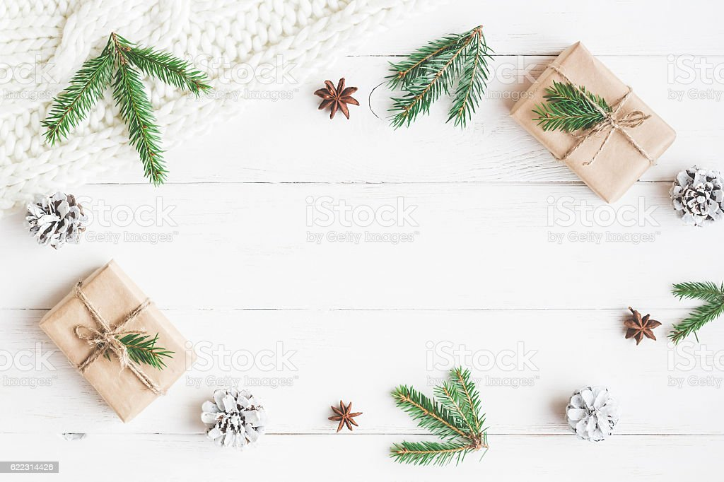 Christmas gift, knitted blanket, pine cones, fir branches. Flat lay stock photo