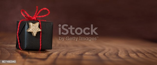 istock Christmas gift on an empty table 607460340