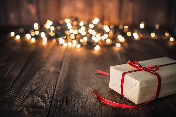 christmas gift on old plank and defocused lights - wärmeplatte stock-fotos und bilder