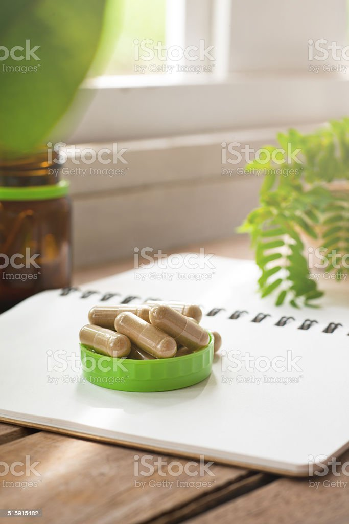 Herb capsule on tablechristmas gift on white background