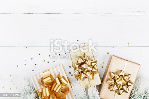Christmas gift or present boxes, fir tree and stars confetti on white wooden table top view. Flat lay.