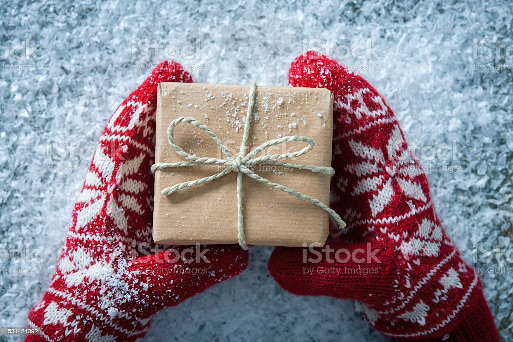 Christmas gift Female hands in winter gloves with christmas gift box Birthday Stock Photo