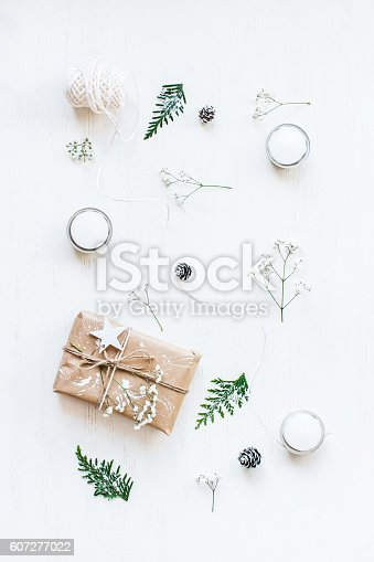 istock Christmas gift, pine cones, thuja branches and gypsophila flowers.Flat lay 607277022