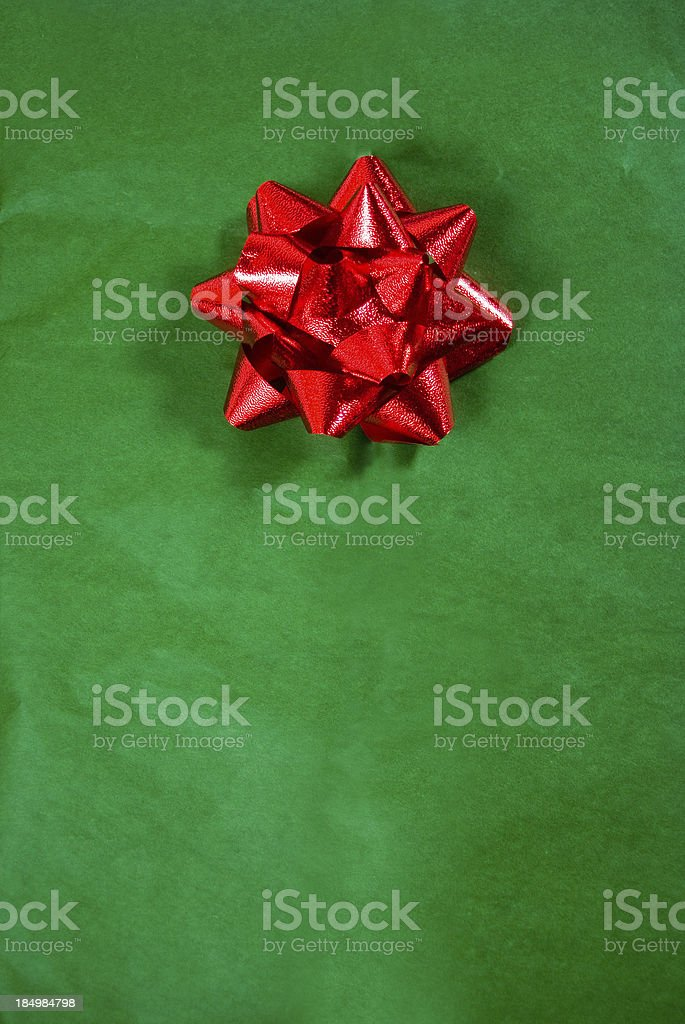 christmas gift; red bow on green wrapping paper stock photo