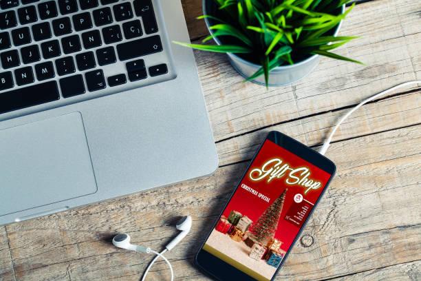 weihnachts-geschenk-shop-app in einem handy-bildschirm, über einen hölzernen tisch - weihnachtsprogramm stock-fotos und bilder