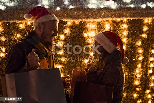 Young woman and young man Christmas gift shopping in city