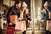 Couple window shopping outdoors in winter city street. Standing in front of a store window.  Wearing warm clothing. Vienna, Austria. Smiling and talking.