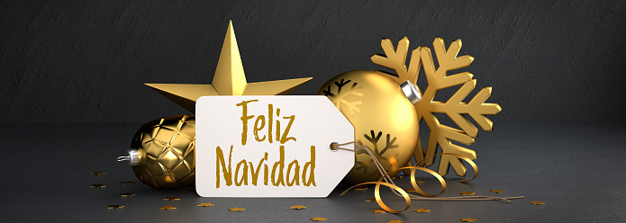 """Christmas - Gift Tag with the Spanish message """"Feliz Navidad"""" (Merry Christmas) on a black stone background leaning against gold colored christmas ornaments. Banner size"""
