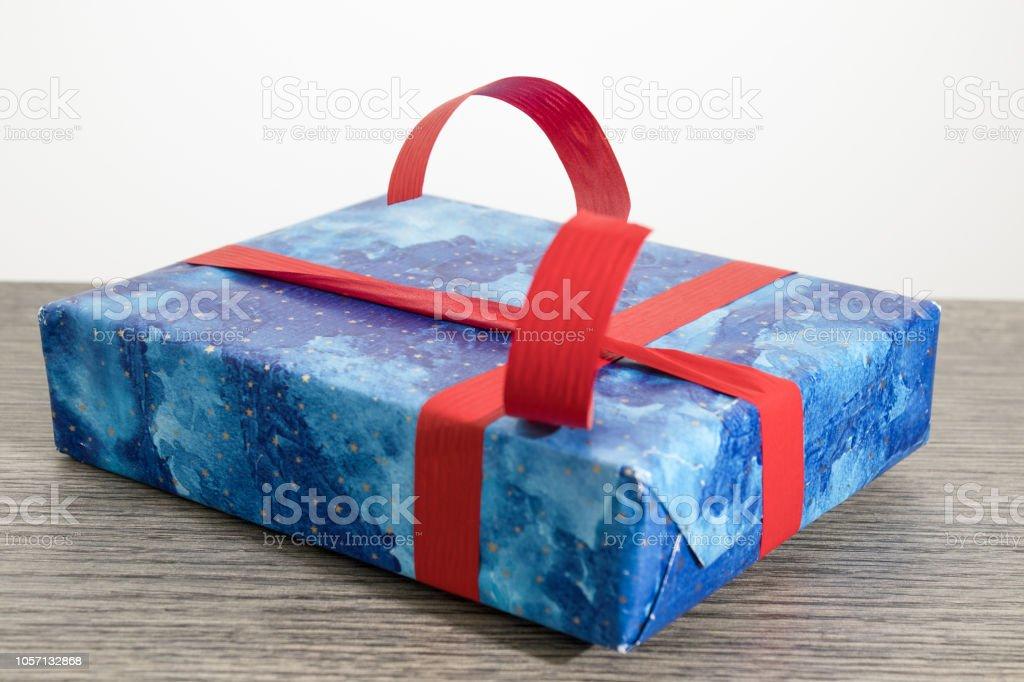 Noel hediyesi Mavi kağıt ve bir ahşap masa kompozisyon üzerinde kırmızı kurdele ile stok fotoğrafı