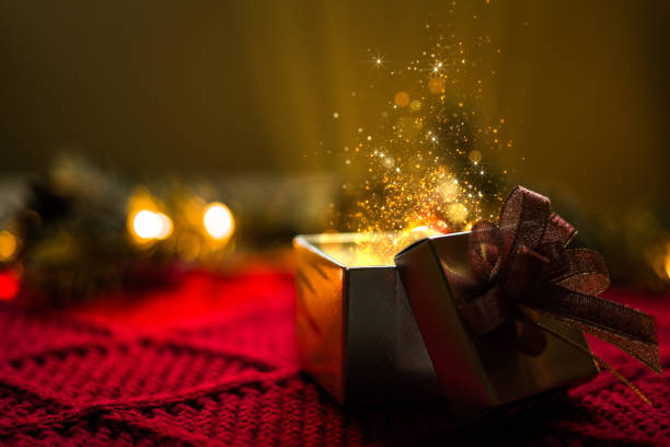 Christmas gift with gold particles magic lights stock photo
