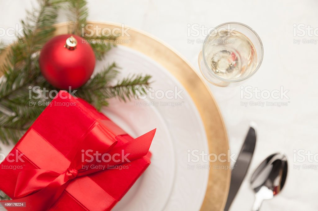 Christmas Gift with Place Setting at Elegant Formal Table stock photo