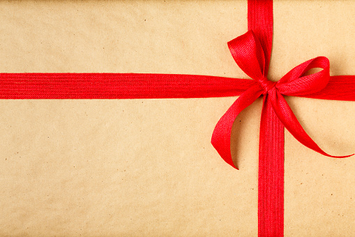 christmas gift with recycled wrapping paper and red bow