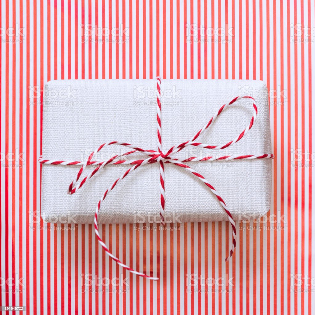 Christmas gift with red ribbon on stripes surface. Top view. Square. stock photo